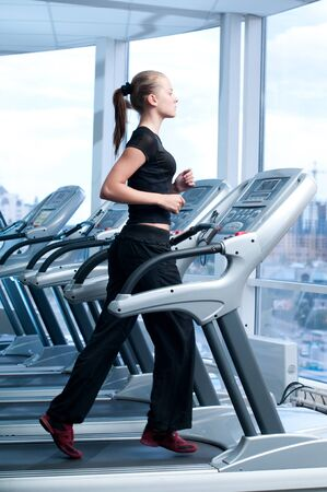 Young woman at the gym exercising. Run on on a machine. photo