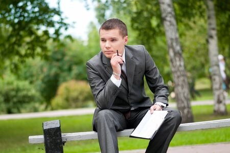 Young business man waiting for meeting, working with papers at green park. Student. photo