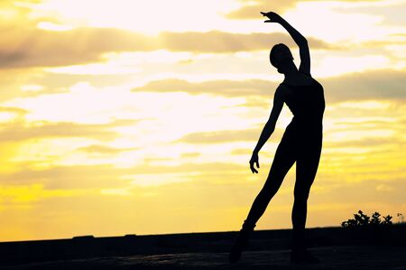 Silhouette photo of dancing woman in modern pilates style over sunset landscape. Yoga photo