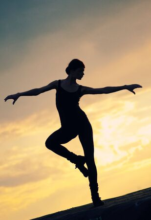 Silhouette photo of dancing woman in modern pilates style over sunset landscape. Yoga Stock Photo - 8715512