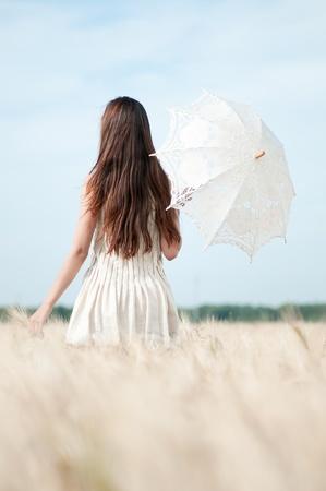 soledad: Hermosa mujer triste y solitaria con paraguas caminando en campo de trigo. El tiempo de espera.