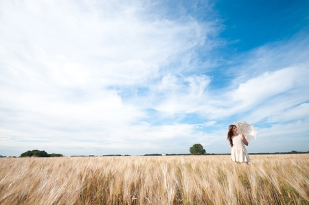 Beautiful sad and lonely woman with umbrella walking in wheat field. Timed. Stock Photo - 8708080