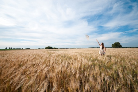 Beautiful sad and lonely woman with umbrella walking in wheat field. Timed. Stock Photo - 8715563