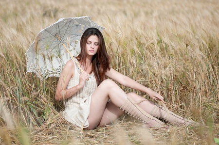 Beautiful sad and lonely woman with umbrella sitting in wheat field. Timed. Stock Photo - 8715601