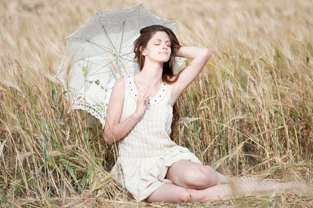 Beautiful sad and lonely woman with umbrella sitting in wheat field. Timed. Stock Photo - 8708060