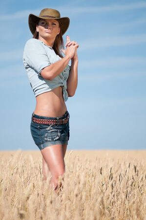 Beautiful cowboy woman with perfect hair and skin posing in country wheat field photo