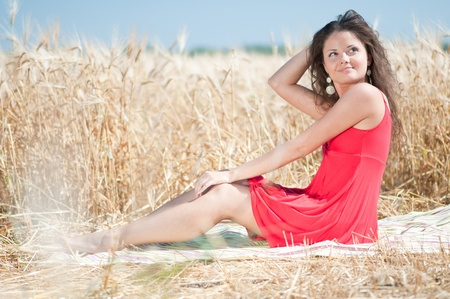 Beautiful woman in red dress with perfect hair and skin posing in wheat field on sunny summer day. Picnic. photo