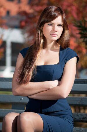 businesswoman suit: Mujer de negocios hermosas j�venes esperando una reuni�n en oto�o Parque de la ciudad. Estudiante