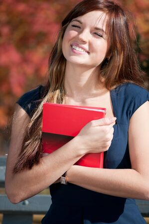 Young beautiful business woman hoding diary at city park. Student photo