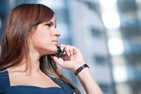 Beautiful businesswoman make call by mobile cell phone. Outdoor, over city. Stock Photo - 8715606