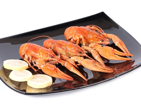 Plate of red boiled lobsters with lemon. Luxury diet meal photo