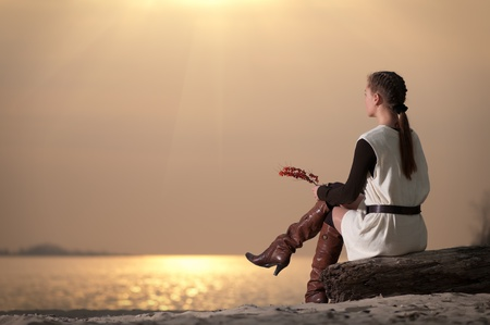Beautiful young lonely woman sitting on sea coast at autumn sunset Stock Photo - 8715470