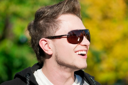 Close up of young casual cheerful man walking in city park photo