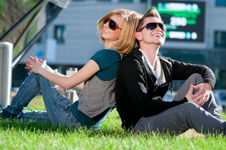 Young emotional happy teenage couple playing on grass in city park Stock Photo - 8715853