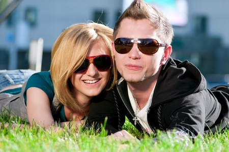 Young emotional happy teenage couple playing on grass in city park photo