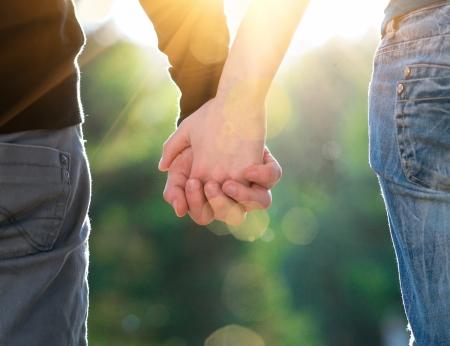 amistad: Brote de concepto de la amistad y el amor de hombre y mujer: dos manos sobre los rayos de sol y de la naturaleza