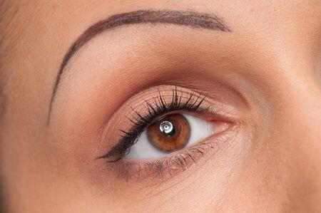 Closeup portrait of beautiful woman face eye makeup zone. Macro