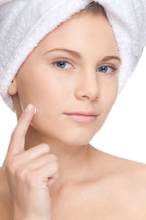 Closeup of young beautiful girl with perfect skin applying cream. Spa Stock Photo - 8715827