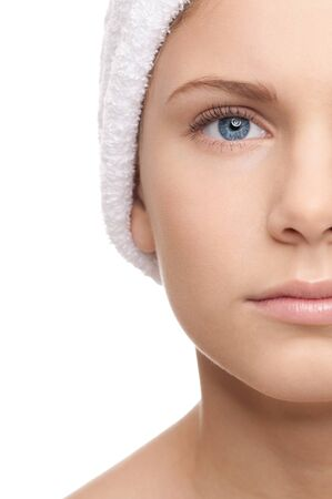 Closeup shoot of half face young beautiful woman with perfect skin and white towel on head photo