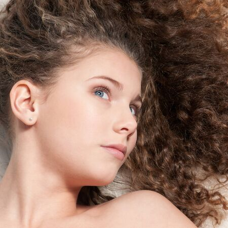 Closeup portrait of young emotional beautiful girl with perfect curly hair. Lying on white fur bed Stock Photo - 8715866