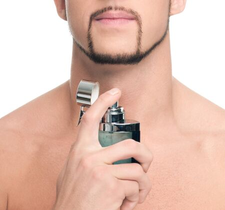 Close up portrait of young handsome man with perfect skin applying perfume. Isolated on white photo