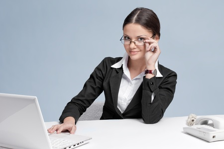 Casual business woman in office working with white table, laptop and phone. Smile. photo