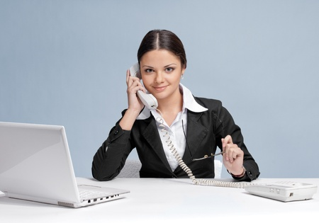 Casual business woman in office working with white table, laptop and talking by phone Stock Photo - 8715841