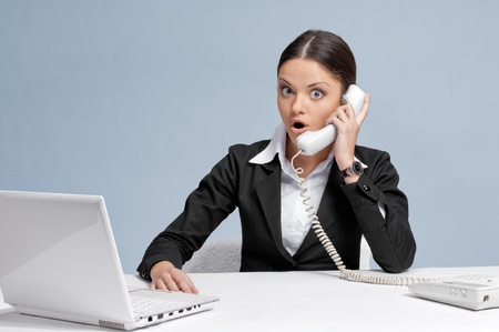 Casual scared  business woman in office working with white table, laptop and talking by phone. Surprise! photo