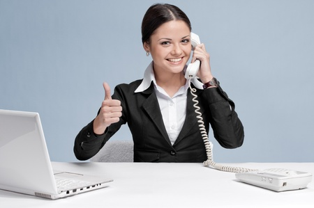 Casual business woman in office working with white table, laptop and talking by phone. Thumbs up! photo