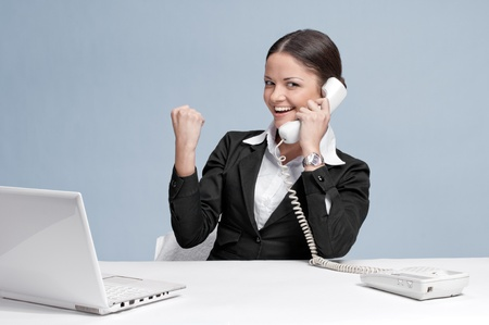 Casual business woman in office working with white table, laptop and talking by phone. Yes! photo