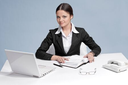 Casual business woman in office working with white table, laptop and diary personal organizer. Smile! photo