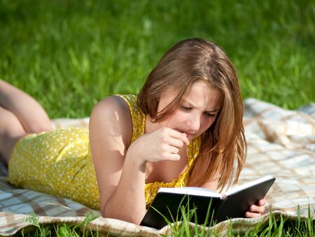 Beautiful young woman reading book outdoor on green grass photo