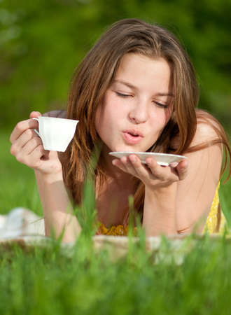 Beautiful young woman drink hot coffee outdoor on green grass photo