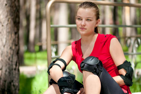 Beautiful young woman rink on roller-skate in green park on sunny summer day photo