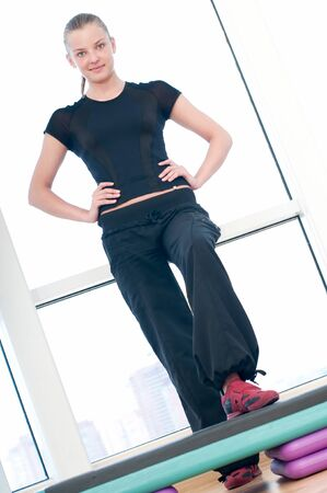 Young woman doing aerobic exercises at the sport gym photo