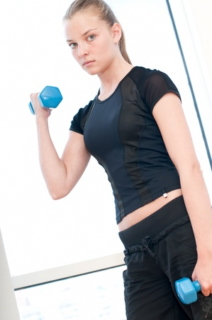 Young woman doing dumbbell exercises at the sport gym photo