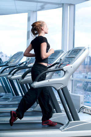 Young woman at the gym exercising. Run on on a machine. Stock Photo - 8876134