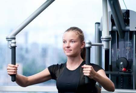 Young woman at the gym exercising on a machine Stock Photo