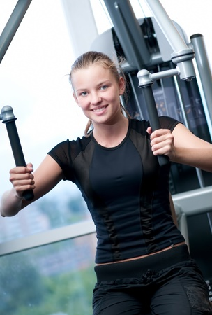 Young woman at the gym exercising on a machine photo