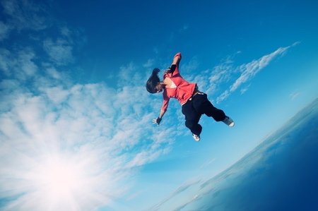 Beautiful sport woman in urban sportswear jumping and fly over blue sky with clouds and sun beam photo