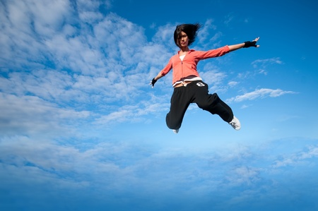 Beautiful sport woman in urban sportswear jumping and fly over blue sky with clouds photo