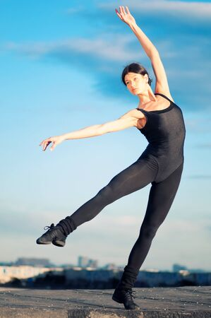dancing woman in modern pilates style over urban city landscape and blue sky. Yoga Stock Photo - 8876037