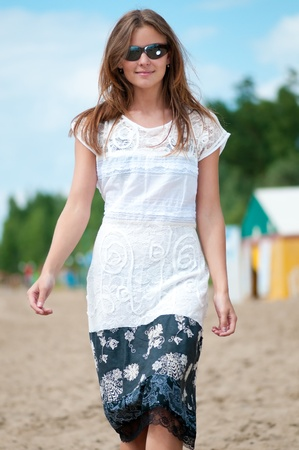 Beautiful young woman in dress and sunglasses walking on sand beach with bag on sunny summer day photo