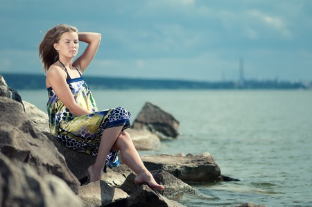Beautiful sad woman in dress sitting on rock over sea at summer storm day photo
