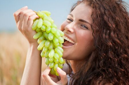 Beautiful woman with perfect hair and skin posing in wheat field and eating green grapes. Picnic. photo