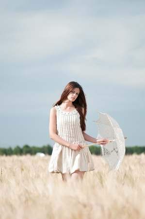 sad lonely girl: Beautiful sad and lonely woman with umbrella walking in wheat field. Timed. Stock Photo