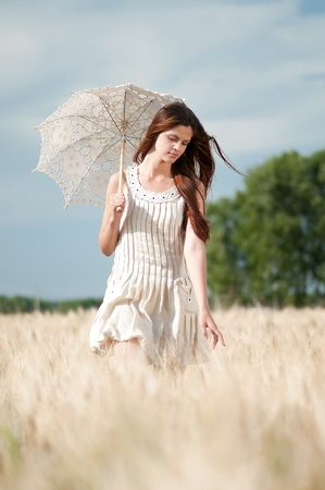 Beautiful sad and lonely woman with umbrella walking in wheat field. Timed. Stock Photo