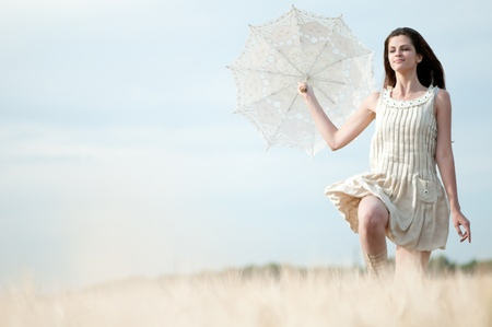 Beautiful sad and lonely woman with umbrella run in wheat field. Timed. photo