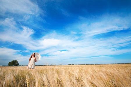 Hermosa mujer triste y solitaria con paraguas caminando en el campo de trigo. El tiempo de espera.