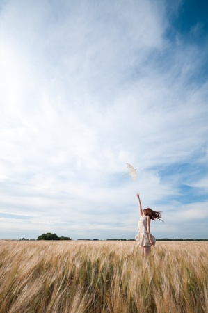 Beautiful sad and lonely woman with umbrella walking in wheat field. Timed. Stock Photo - 8876141